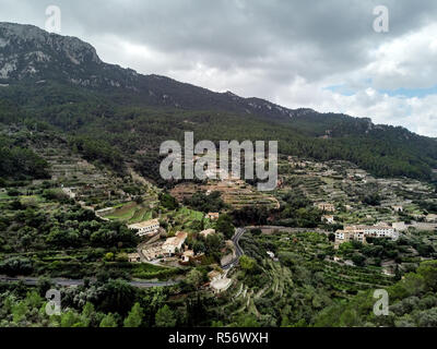 Aerial drone view of small hillside Banyalbufar town on west coast of Mallorca. Surrounded by Tramuntana mountain range Spain - Stock Photo