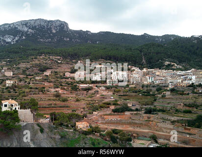 Aerial drone view of small hillside Banyalbufar town on west coast of Mallorca. Surrounded by Tramuntana mountain range. Spain - Stock Photo