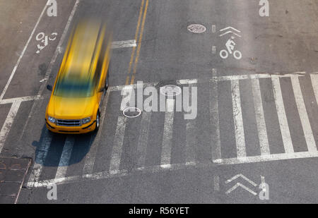 Overhead street view of yellow taxi cab speeding through an intersection crosswalk in New York City - Stock Photo