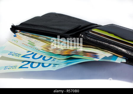 Stack of various of israeli shekel money bills in open black leather wallet - Stock Photo