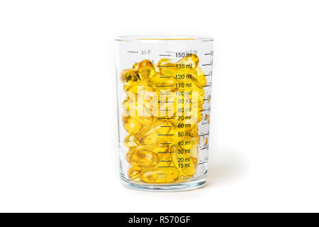 Bright yellow fish oil capsules in the glass measurement on white background shot with studio light - Stock Photo