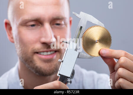 Close-up Of A Man Measuring Gear's Size With Digital Electronic Vernier Caliper On Grey Background - Stock Photo