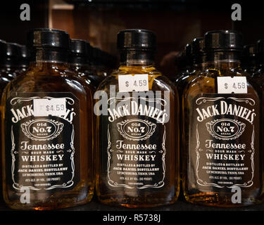 A shelf full of bottles of Jack Daniel's Old No. 7 Tennessee Sour Mash Whiskey for sale in a liquor store. - Stock Photo