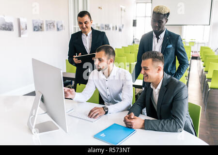 startup business team on meeting in modern bright office interior brainstorming, working on laptop and tablet computer - Stock Photo