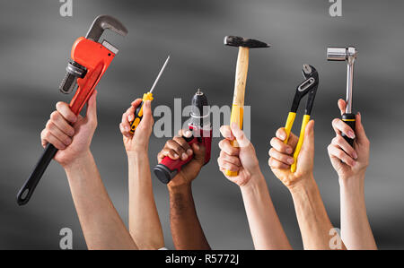 Hands Holding Work Tools - Stock Photo