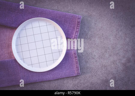 Checked white plate and purple tablecloth, on dark concrete background with copy space. - Stock Photo