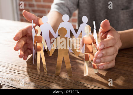 Person Protecting Paper Cut Out Figure - Stock Photo