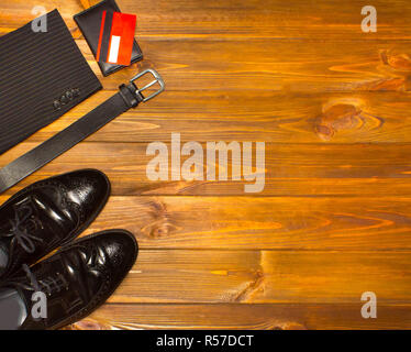 The elegant male set: men's shoes, leather belt, on the wooden background.
