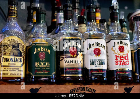 Whiskey Liquior Bottles Lined up on a Shelf - Stock Photo