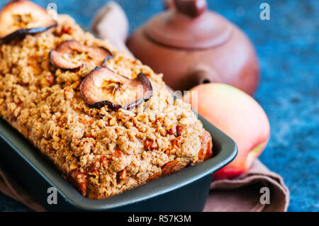 Homemade apple crumble cake served on a wire rack on a white sto - Stock Photo