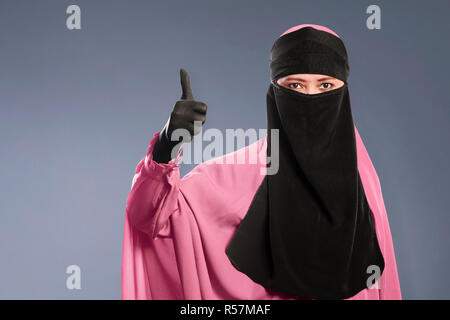 Portrait of asian muslim woman in hijab showing fine sign - Stock Photo
