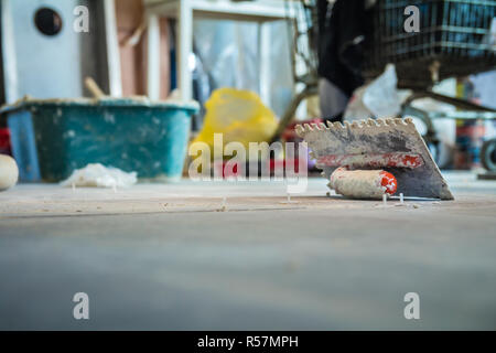 Trowel on the floor in construction site - Stock Photo