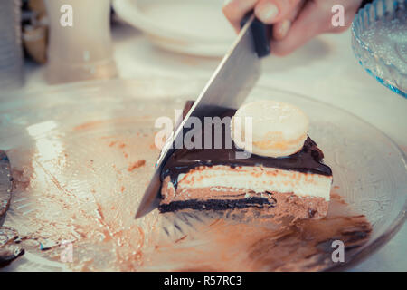 Female hand with a knife slicing chocolate-vanilla mousse cake with Glsaz of chocolate and white macaroon on it. - Stock Photo