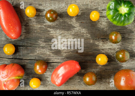 ripe tomatoes with water on a board - Stock Photo