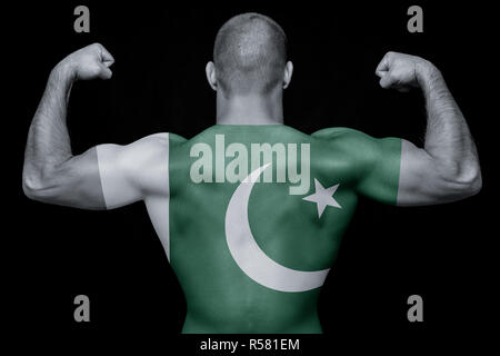 The back of a young athletic man wearing a T-shirt with the national flag of Pakistan on a black isolated background. The concept of national pride an - Stock Photo