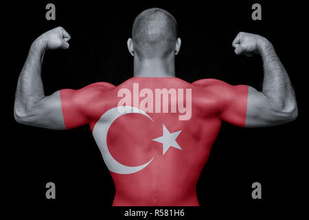 The back of a young sporty man wearing a T-shirt with the national flag of Turkey on a black isolated background. The concept of national pride and pa - Stock Photo