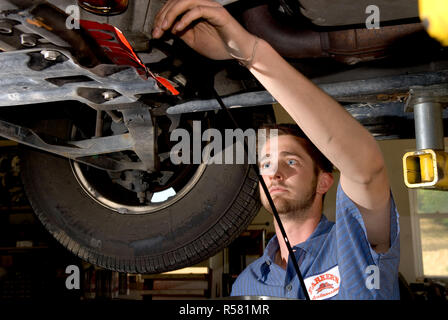 2007 - Mechanic in Maryland providing routine maintainance by draining motor oil from a car during an oil change - Stock Photo
