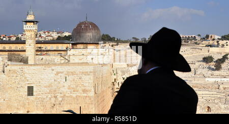 view of the old city of jerusalem with the silhouette of an orthodox jew in the foreground - Stock Photo