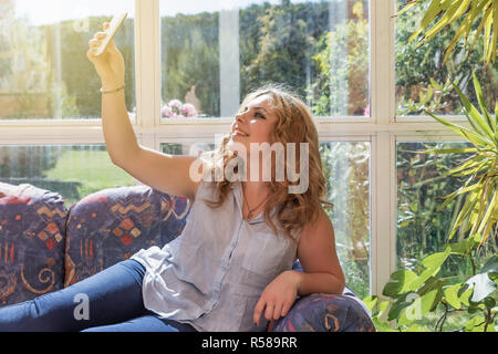Young pretty girl making selfie lying on the sofa - Stock Photo