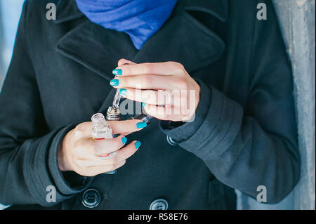 portrait of young beautiful woman with white hair, in a black coat, a skirt and a black hat, smoking an electronic cigarette, runs vape juice electronic cigarette. He holds a mechanical mod with RDA. - Stock Photo