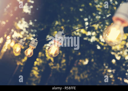 hanging decorative string lights for outdoor party - Stock Photo