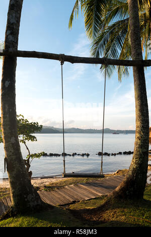 Wooden swing chair hanging on tree near beach at island in Phuket, Thailand. Summer Vacation Travel and Holiday concept. - Stock Photo
