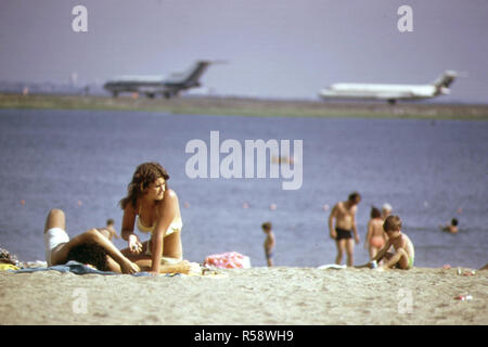 1970s - Constitution Beach - Within Sight and Sound of Logan Airport's Takeoff Runway 22r (pretty woman on beach 1970s) - Stock Photo