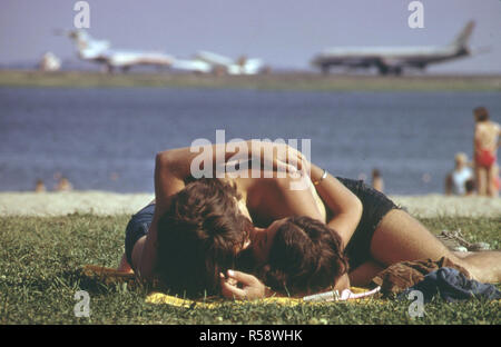 1973 - Constitution Beach - Within Sight and Sound of Logan Airport's Takeoff Runway 22r - Young man and woman kissing in a park - Stock Photo