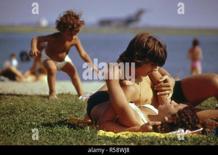 Constitution Beach - Within Sight and Sound of Logan Airport's Takeoff Runway 22r - Young man and woman hug / embrace lying on the ground - Stock Photo