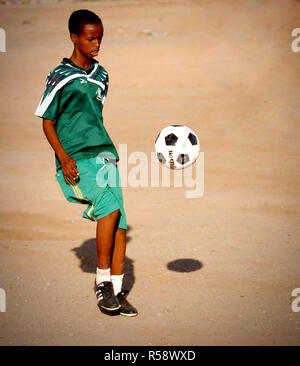 A boy from the Djibouti City's Boy's Orphanage kicks a soccer ball donated by U.S. Military Service Members deployed with Combined Joint Task Force - Horn of Africa (CJTF-HOA).  - Horn of Africa is a unit of U.S. Central Command that conducts operations and training to assist Partner nations to combat terrorism in order to establish a secure environment and enable regional stability. - Stock Photo