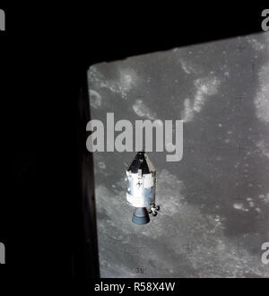 (30 July 1971) --- A view of the Apollo 15 Command and Service Modules (CSM) in lunar orbit as photographed from the Lunar Module (LM) just after rendezvous. The lunar nearside is in the background. This view is looking southeast into the Sea of Fertility. The crater Taruntius is at the right center edge of the picture. - Stock Photo