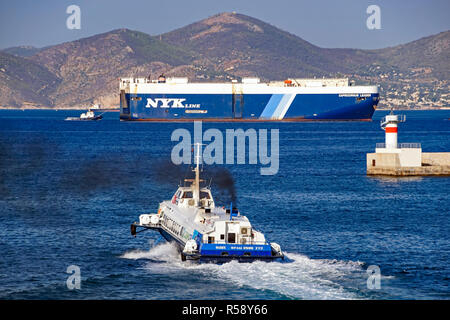 Hellenic Seaways Flying Dolphin 17 leaving port of Piraeus Athens Greece Europe with NYK Line Capricornus Leader behind - Stock Photo
