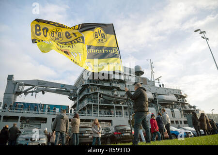 Wilhelmshaven, Germany. 30th Nov, 2018. A member of a naval soldier is standing in front of the 'Bonn' task force supplier at the naval port with an oversized flag of the football club 'BVB - Borussia Dortmund' shortly before the ship leaves for the Aegean Sea. Credit: Mohssen Assanimoghaddam/dpa/Alamy Live News - Stock Photo