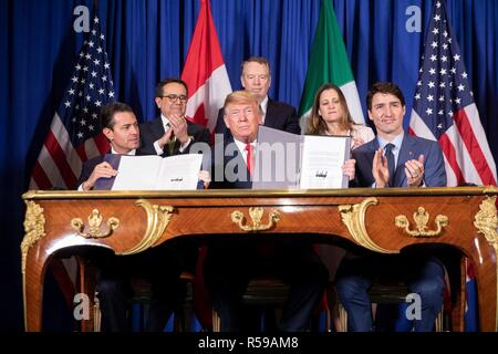 U.S. President Donald Trump, center, and Mexican President Enrique Pena Neto, left, hold up the signed new NAFTA trade agreement called USMCA as Canadian Prime Minister Justin Trudeau, applauds November 30, 2018 in Buenos Aires, Argentina. - Stock Photo