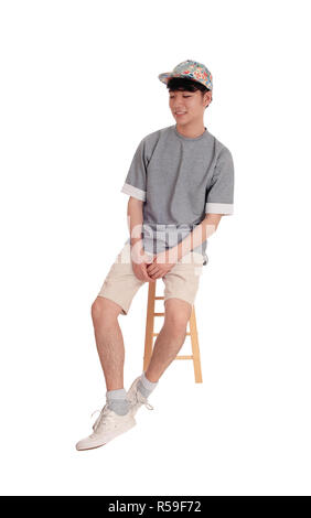 Asian man sitting and smiling. - Stock Photo