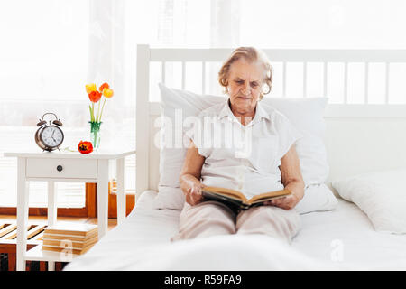 Elderly woman sitting comfortably in bed reading her favourite book - Stock Photo
