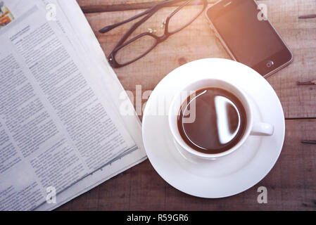Topview coffee cup with newspaper and glasses and smart phone on the table with sunlight from the window - Stock Photo
