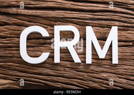 White CRM Text On Wooden Table - Stock Photo
