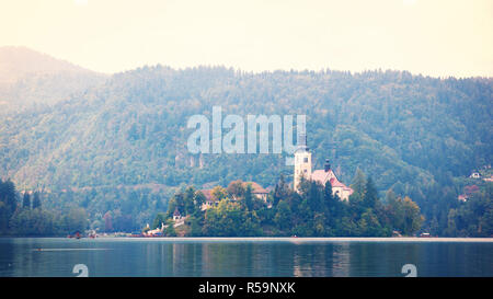 Old church on small island in the middle of lake with gondolas flowing on watter, Bled Lake Slovenia - Stock Photo