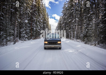 Old car standing in the middle of empty road going through big forest coverd with white snow, Banff national park Canada - Stock Photo