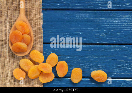 Dried apricots in spoon and near on blue wooden table, top view with copy space - Stock Photo