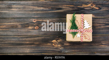 Christmas vintage, toned gift box wrapped in recycled paper, with ribbon top view with copy space on rustic background. Holiday concept. - Stock Photo
