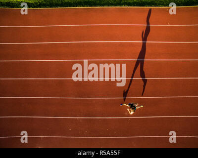 Shot of a young male athlete training on a race track. Sprinter running on athletics tracks seen from above. - Stock Photo