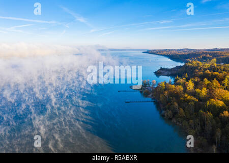 Morning fog over Lake Starnberg, Restaurant Kleines Seehaus in St. Heinrich near Münsing, drone shot, Fünfseenland - Stock Photo