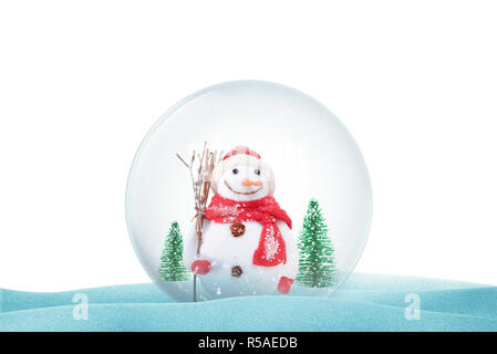 Isolated Christmas magic ball on snow with snowman and trees. Christmas decorative ball with snow falling. - Stock Photo