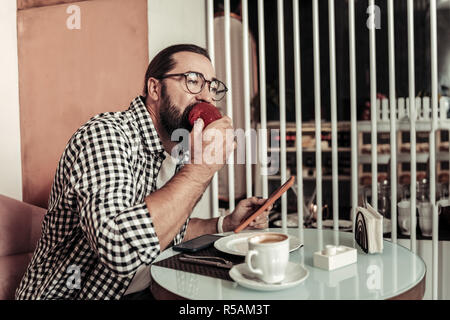 Breakfast time. Pleasant nice man holding a tablet while having a breakfast in the cafe - Stock Photo