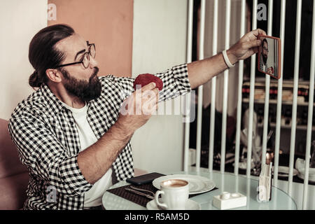 Funny selfie. Happy positive man looking into the camera while taking a selfie with a cake - Stock Photo