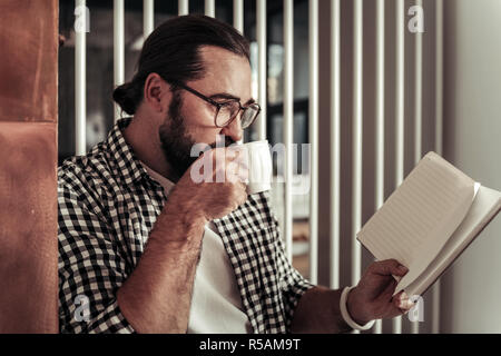 Morning drink. Nice positive man taking a sip of coffee while reading his notebook - Stock Photo