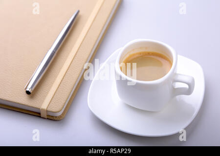 stylish notebook, ballpoint pen and white cup with a fragrant espresso coffee on the office desk - Stock Photo