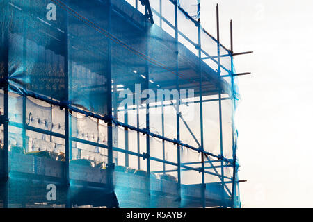Blue scaffolding with safety netting in nice sunlight in the Netherlands - Stock Photo